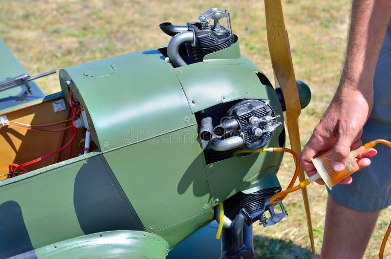 Werktuigkundige die de motor model militaire vliegtuigen van brandstof voorzien stock foto's