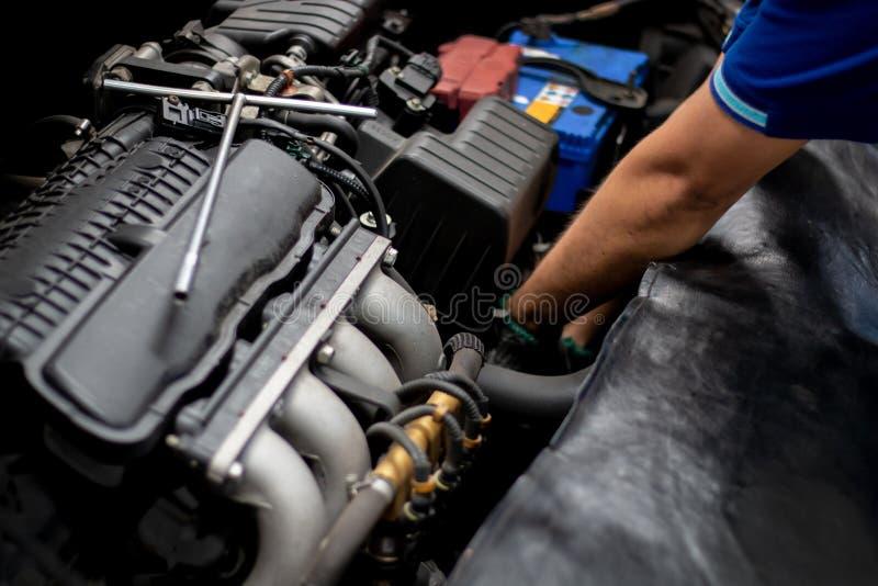 Werktuigkundige die de motor van een auto in autoreparatie controleren stock afbeeldingen