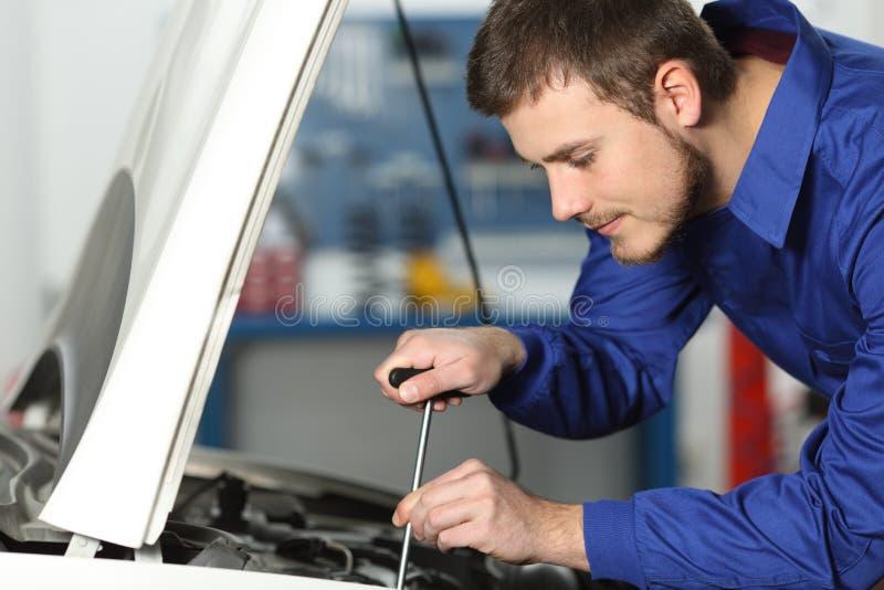 Werktuigkundige die een auto in een workshop herstellen stock afbeelding