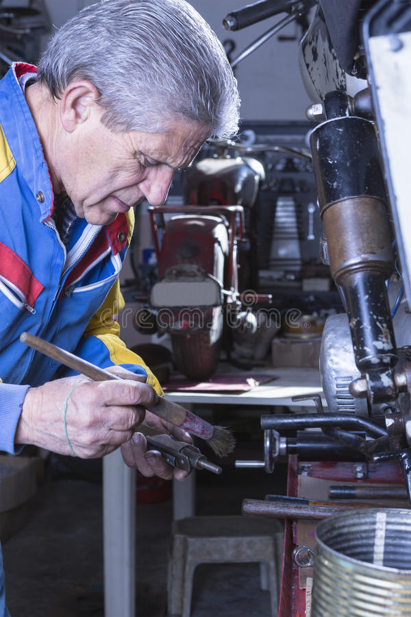 Werktuigkundige die een motorvoetsteun schoonmaken stock foto's