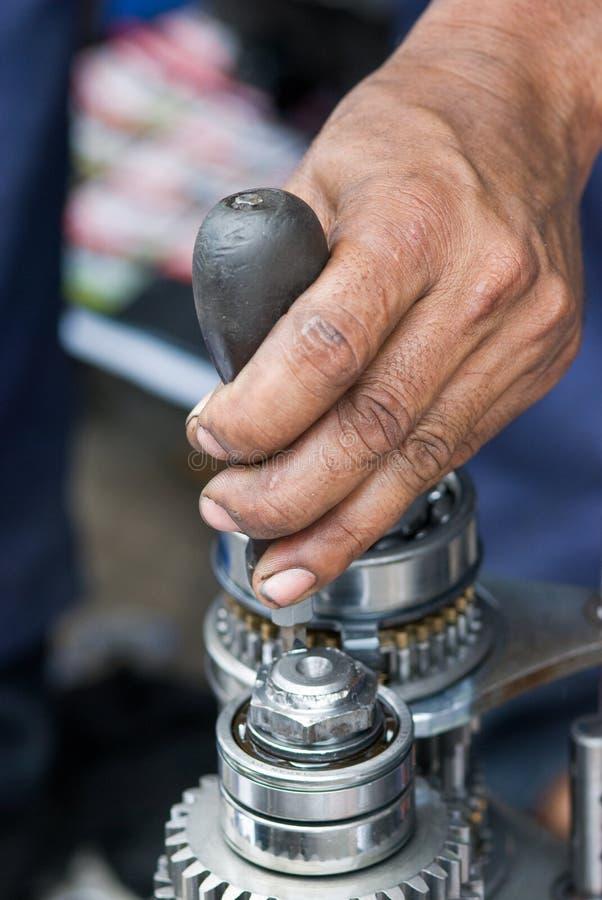 Werktuigkundige die een versnellingsbak herstelt stock afbeelding