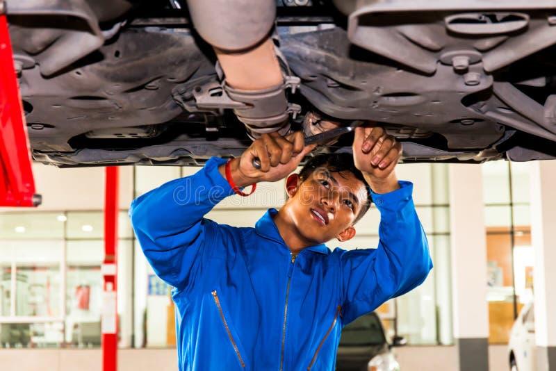 Werktuigkundige die en zich onder een opgeheven auto met exemplaarruimte bevinden bevestigen royalty-vrije stock foto