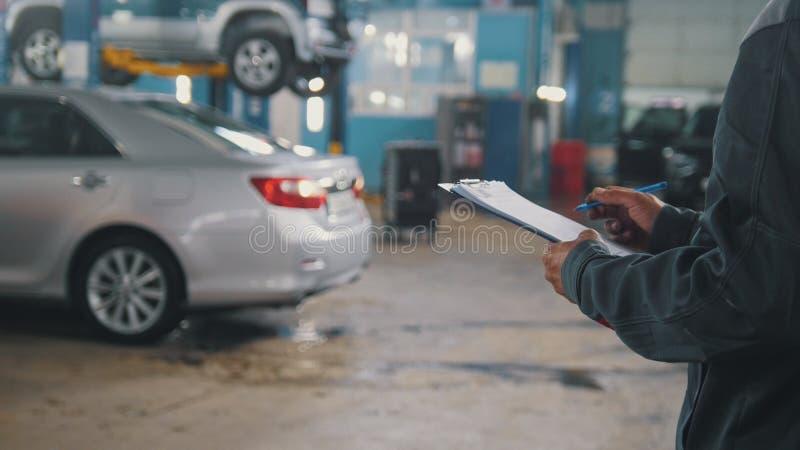 Werktuigkundige die het controleren van een auto in een garageworkshop doen stock foto
