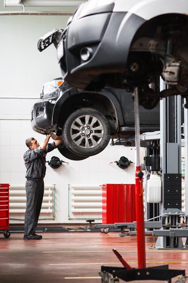 Werktuigkundige die motorbescherming op opgeheven auto verwijderen stock fotografie