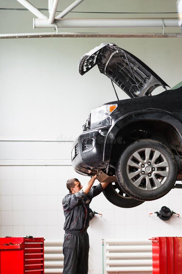 Werktuigkundige die onder auto in benzinestation werken stock afbeeldingen