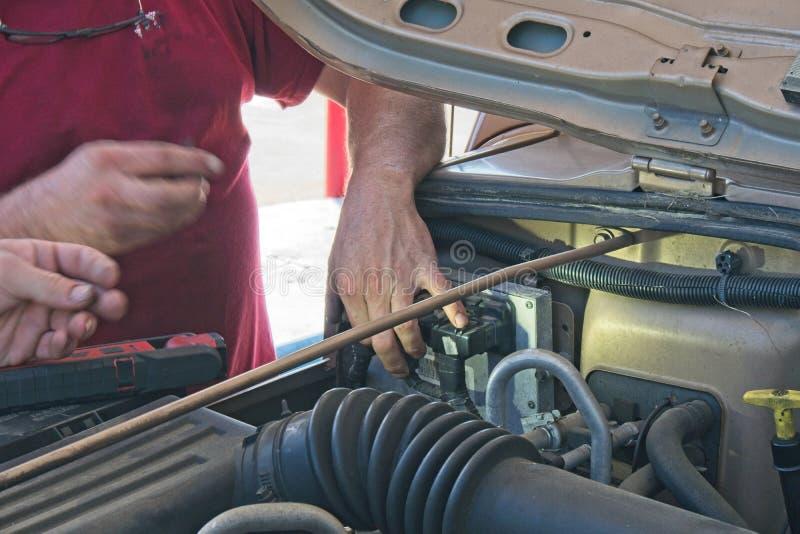Werktuigkundige die onder de kap van een auto in een benzinestation werken royalty-vrije stock afbeelding