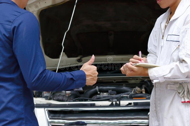 Werktuigkundige en klant tussen het herstellen van motor van auto bij auto de dienstgarage stock afbeelding