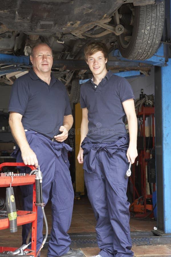 Werktuigkundige en leerling die aan auto werken stock afbeelding