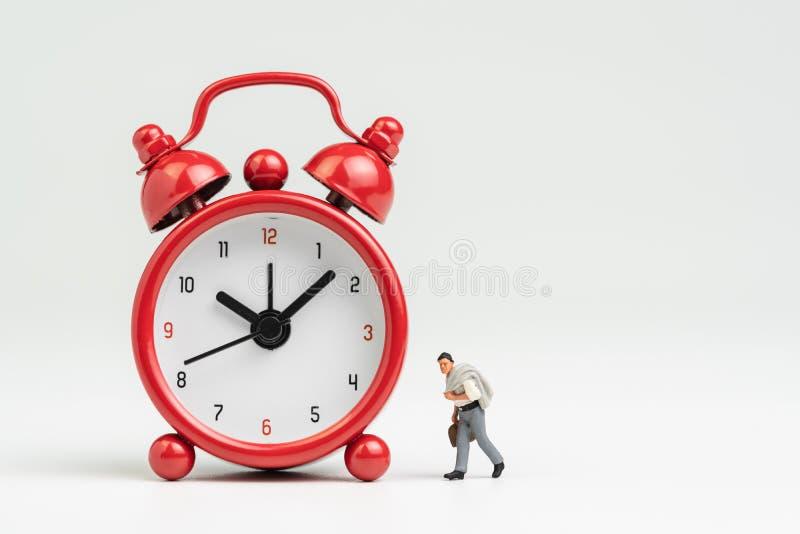 Werkuren, tijd gaan werken of het concept van het vergaderingsprogramma, miniatuurcijferzakenman met kostuum en koffer die lopen  stock afbeeldingen