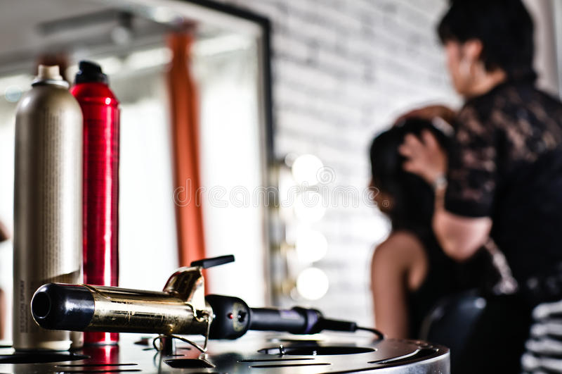 Werkzeuge der Schönheit (Haarspray und Brennschere) lizenzfreies stockbild