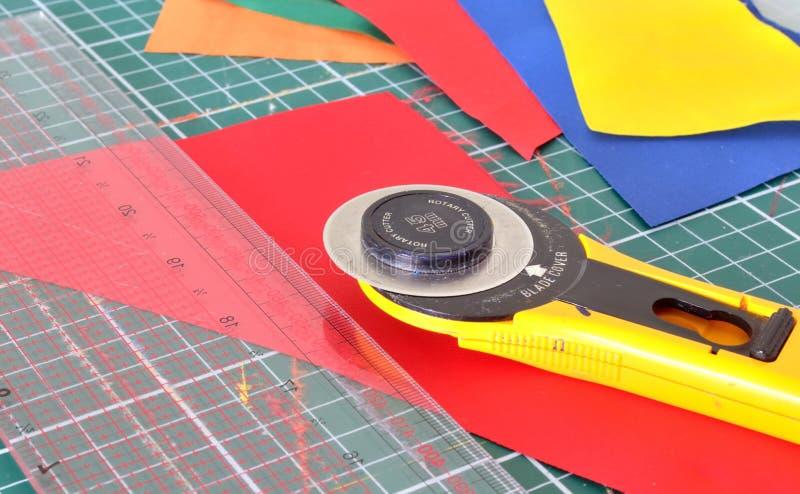 Werkzeuge für Patchwork: Messer, Machthaber und Herausschneiden der Matte stockfotografie