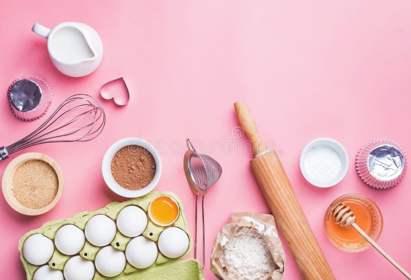 Werkzeuge und Bestandteile für die Herstellung der süßen Bäckerei wie Torte oder kleine Kuchen lizenzfreie stockbilder