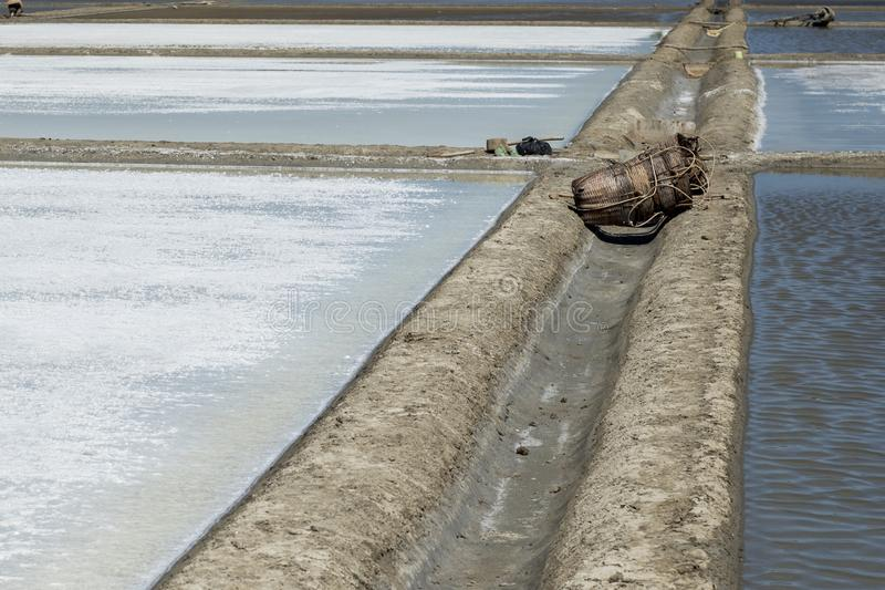 Werkzeuge und gesponnene Weidentaschen gelassen in den leeren Salzsümpfen am Nachmittag an Dose Gio, Vietnam stockbilder