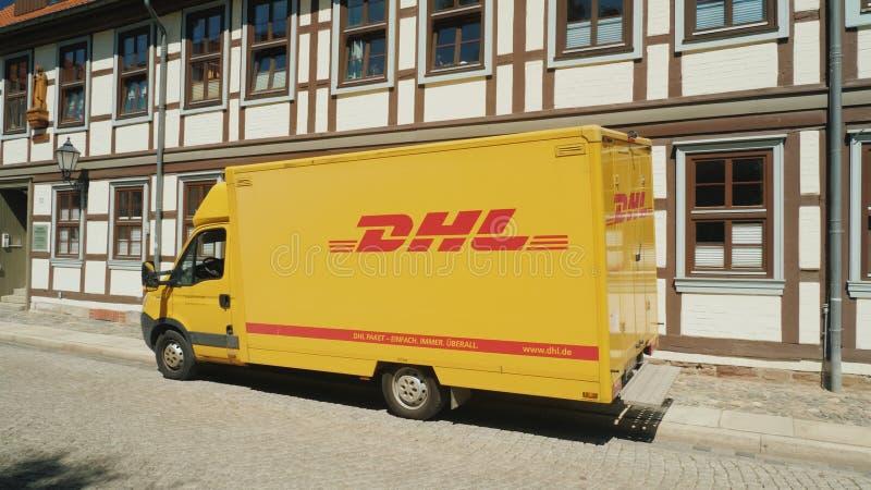 Wernigerode Tyskland, Maj 2018: Vagnen av postgången DHL står på en tyst gata i en tysk stad på royaltyfri bild