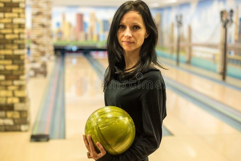 Werpt het vrouwen speelkegelen een bal op de strook royalty-vrije stock foto