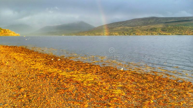 Rainbow on Scottish Loch. With the sun shining over the water royalty free stock photo