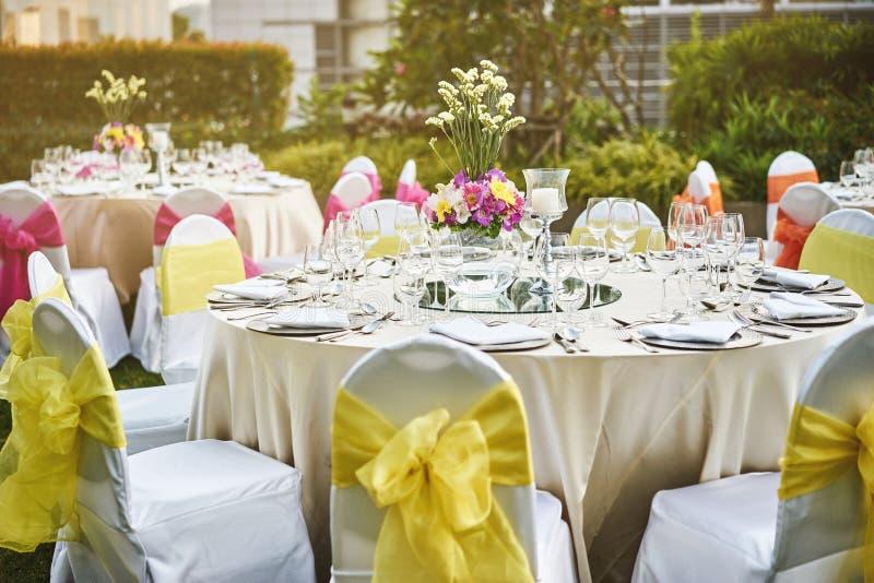 Wesele obiadowego stołu położenie z kwiat dekoracją i biel pokrywą przewodniczy żółtą szarfę obrazy royalty free