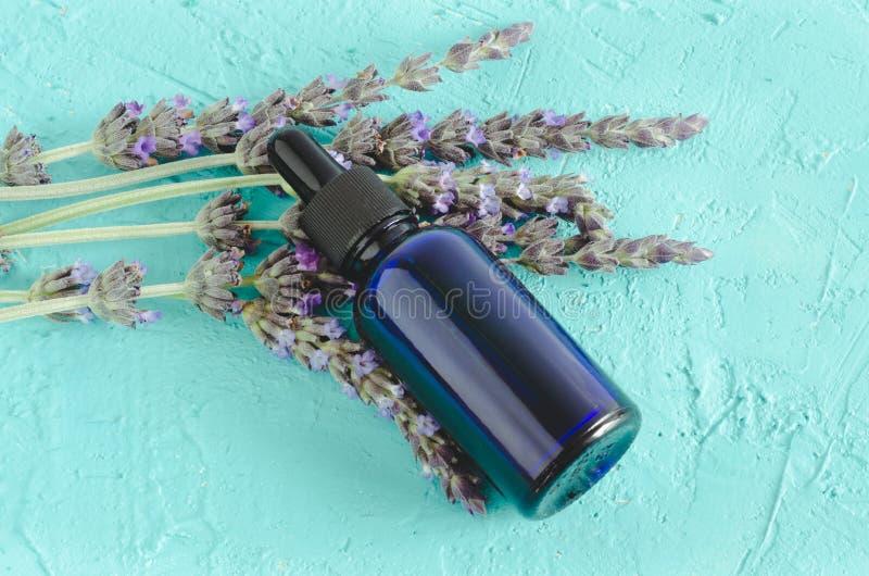 Wesentliches Schmieröl des Lavendels Blumen und Flasche mit Pipette auf blauem Hintergrund stockfotografie