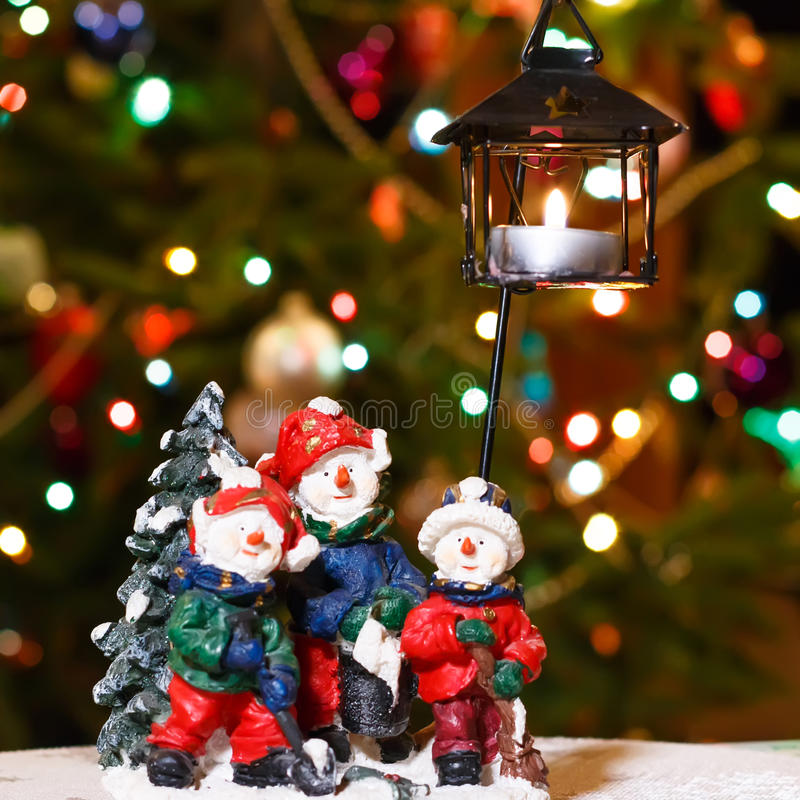 Wesoło bałwanu candleholder z płonącą świeczką przed choinką zaświeca zdjęcie stock
