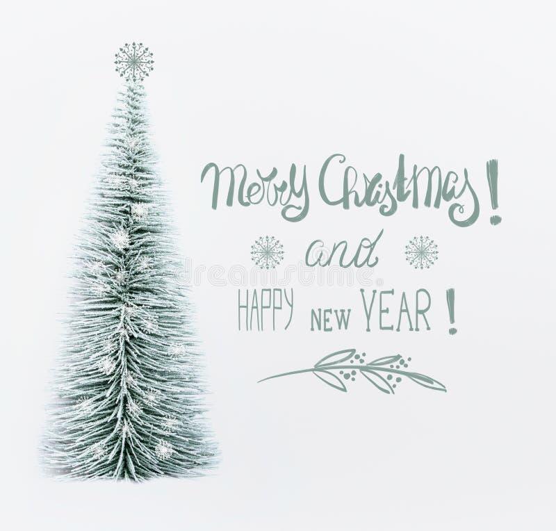 Wesoło boże narodzenia i Szczęśliwa nowy rok kartka z pozdrowieniami z teksta literowaniem i dekoracyjną sztuczną choinką obraz stock