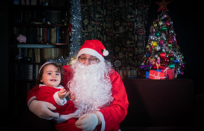 Wesoło boże narodzenia i szczęśliwi wakacje! Śliczna małe dziecko dziewczyna, Święty Mikołaj siedzi blisko rozjarzonego jedlinowe zdjęcie royalty free
