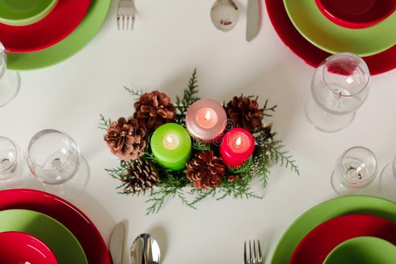 Wesoło boże narodzenia i Szczęśliwy nowy rok! Тable ustawia świątecznego wystrój zieleń, czerwoni naczynia, świeczki i jedlinowi obrazy stock