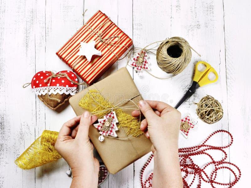 Wesoło boże narodzenia - kobieta wręcza opakunkowego prezenta pudełko, dekoracje i obraz stock