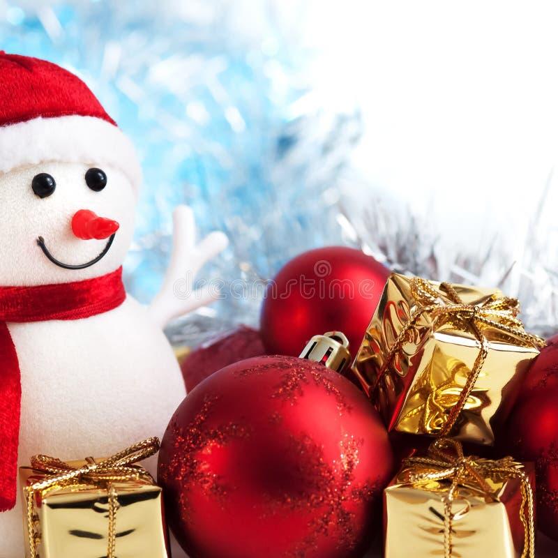 Wesoło boże narodzenia, nowy rok, bałwan, prezenty w złotych pudełkach i czerwone piłki na bokeh tle, błękitnym i białym obrazy stock