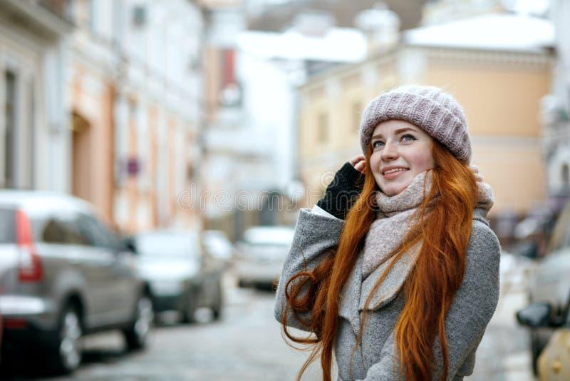 Wesoło czerwona z włosami kobieta jest ubranym ciepłej zimy odprowadzenia odzieżowego puszek fotografia stock
