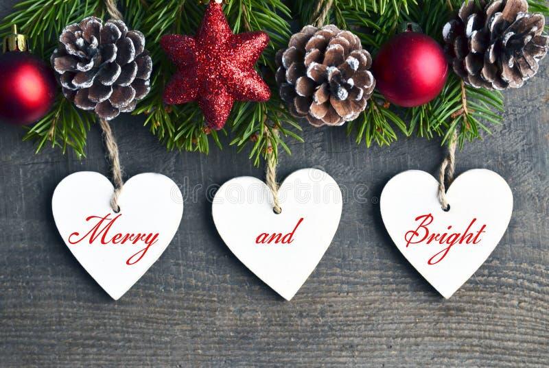Wesoło i Jaskrawy Bożenarodzeniowa dekoracja z jedlinowym drzewem, sosnowymi rożkami i białymi drewnianymi sercami na starym drew zdjęcie royalty free