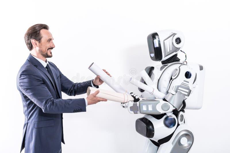 Wesoło uśmiechnięty kierownik współpracuje z cyborgiem fotografia stock