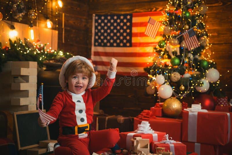 Wesołych Świąt i szczęśliwego Nowego Roku w Stanach Zjednoczonych Ameryki Santa helper z amerykańską flagą choinka i obrazy royalty free