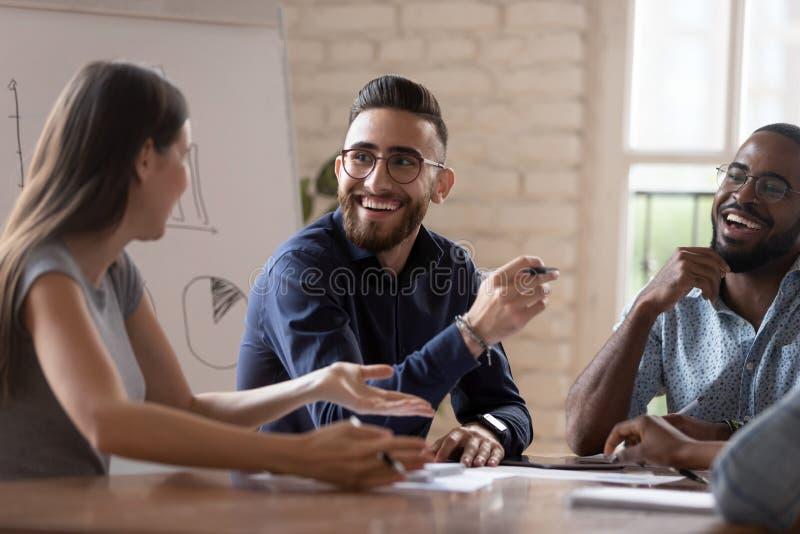 WesoÅ'ych i zróżnicowanych kreatywnych grup biznesowych rozmawiajÄ…cych na spotkaniu grupy zdjęcia stock