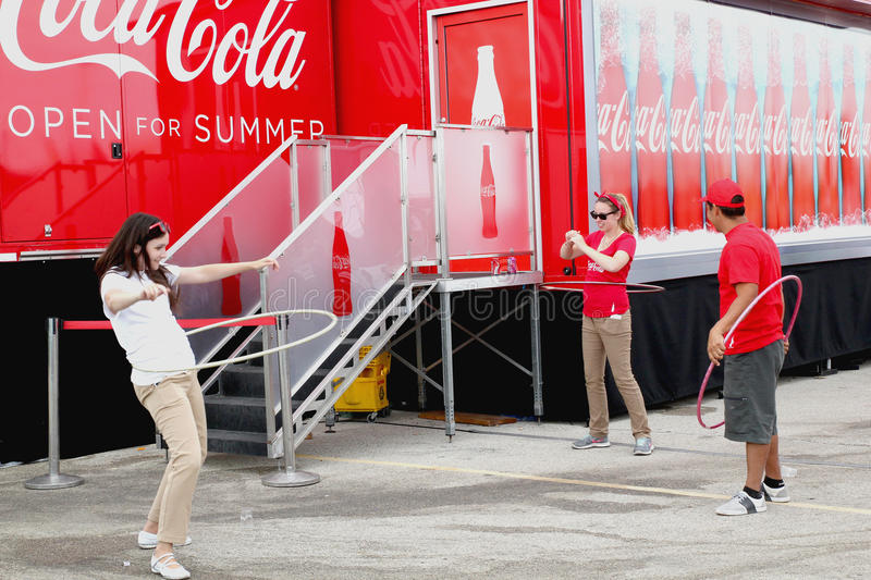 West Allis, WI State Fair 2013. Three employees of the Coca Cola stand were entertaining some of the fair fans with their example of how to correctly use a hoola stock photography