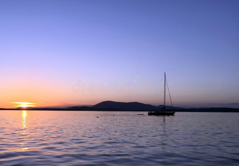 Sailboat at Sunset at Sidney Spit, off the coast of Vancouver Island, BC stock images