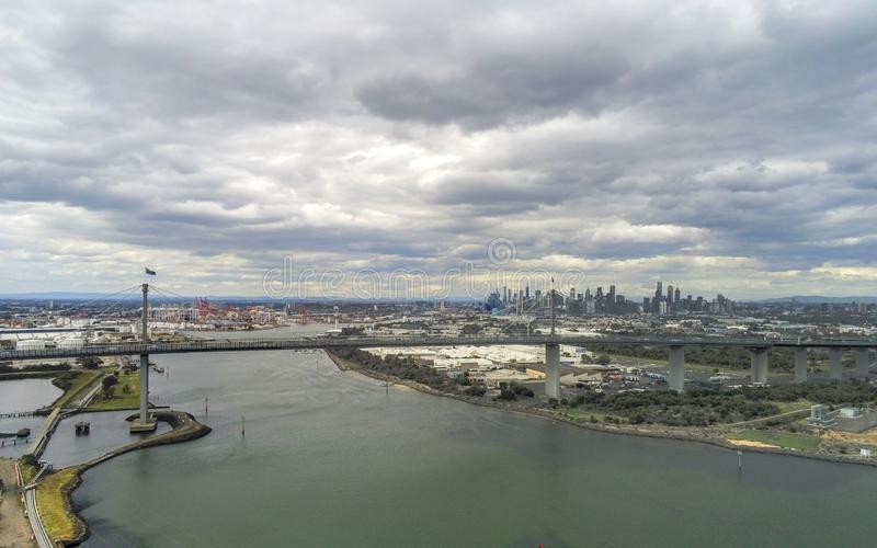 West Gate Bridge and Melbourne city. Aerial view of the West Gate Bridge and Melbourne city skyline with dark storm clouds stock images