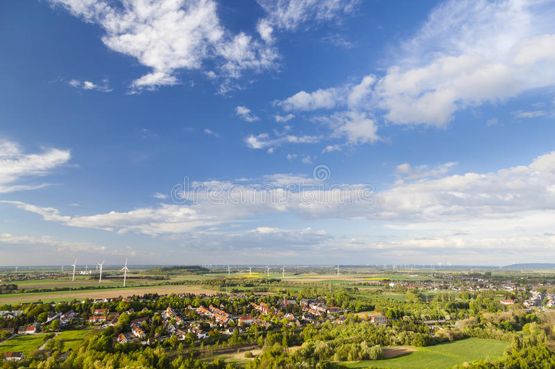 West German Wind Energy Landscape. Flat west German landscape near Aachen and Herzogenrath with lots of wind turbines and some clouds on blue sky royalty free stock photography