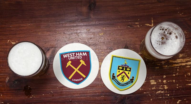 West Ham London vs. Burnley. Football team logos on beer mat at the pub with pints of beer stock image