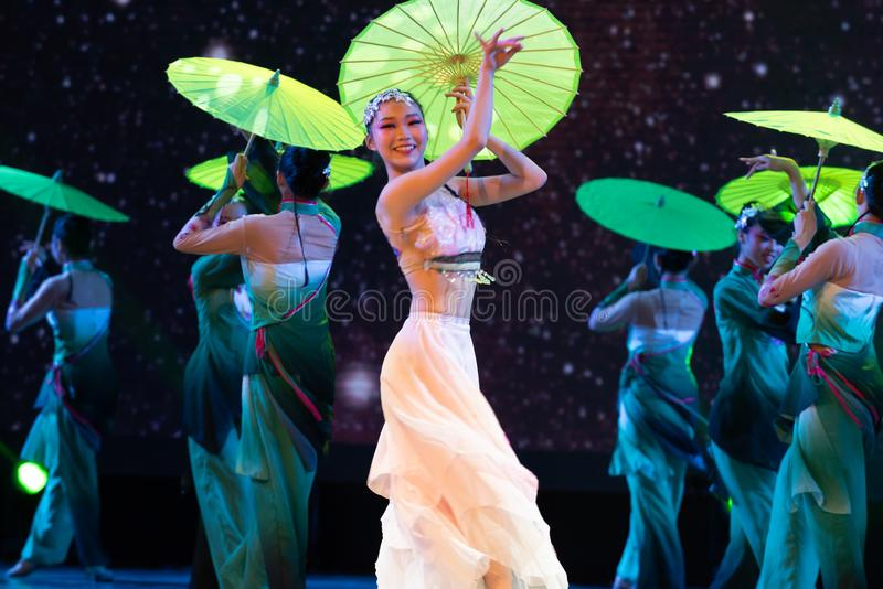 Oiled paper umbrella-In the spring of the west lake-Chinese classical dance. By the west lake in hangzhou, a pair of graceful young girls came to pick mulberry royalty free stock photography