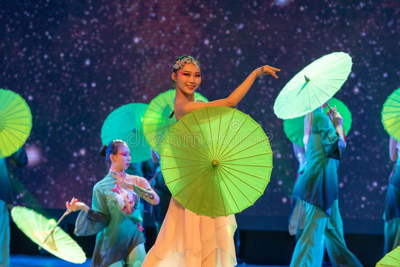 Oiled paper umbrella-In the spring of the west lake-Chinese classical dance. By the west lake in hangzhou, a pair of graceful young girls came to pick mulberry royalty free stock images