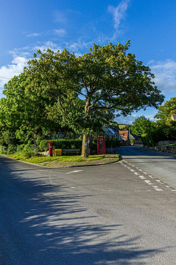 West Lulworth, Dorset / United Kingdom - June 20, 2019: A view of a rural village road intersection with letter box, phone boot. And majestic huge tree under a royalty free stock photos