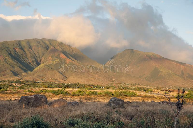 West Maui Mountains at Sunset. Sun sets as rain clouds disperse behind the West Maui Mountains. Maui is one of the Hawiian Islands stock photos