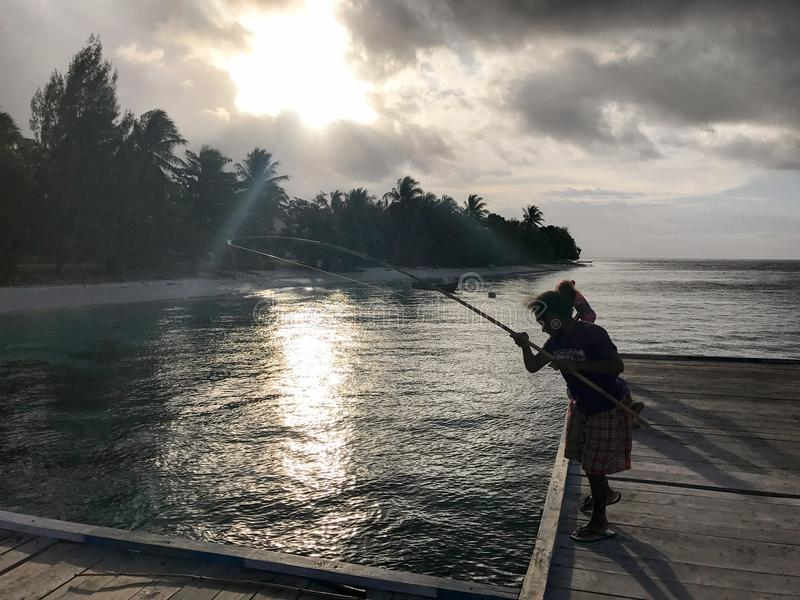 Indigenous woman fishing on pier at sunset royalty free stock photos