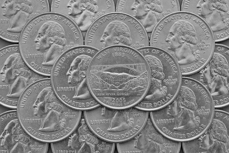 West Virginia State and coins of USA. Pile of the US quarter coins with George Washington and on the top a quarter of West Virginia State stock images