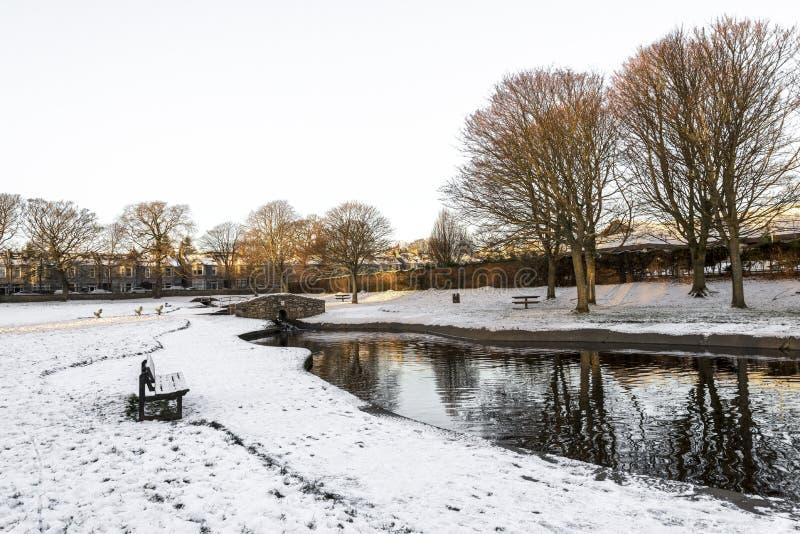 Westburn park mit einem kleinen Teich, Steinbrücke und Bank während der Wintersaison, Aberdeen, Schottland stockbild