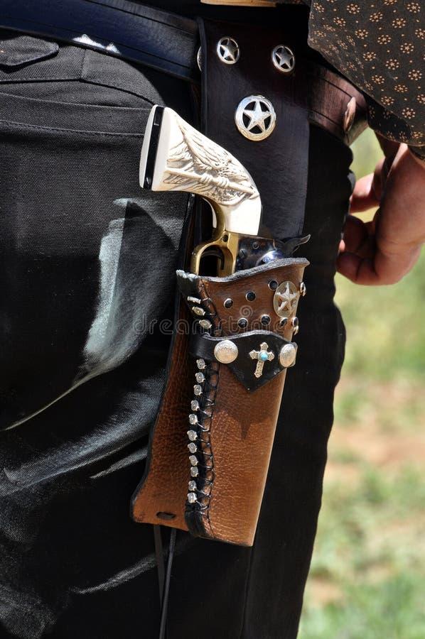 Westelijk pistoolkanon met de greep van het ivoorhandvat in het kanonriem van het leerholster versleten door oude het westencowbo royalty-vrije stock foto's
