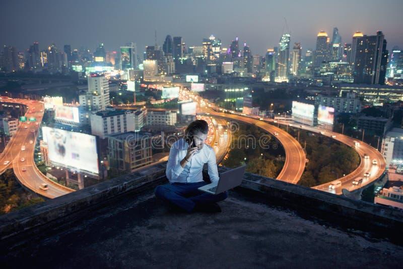 Westelijke zakenman die telefoon en laptop met stadsachtergrond met behulp van stock foto