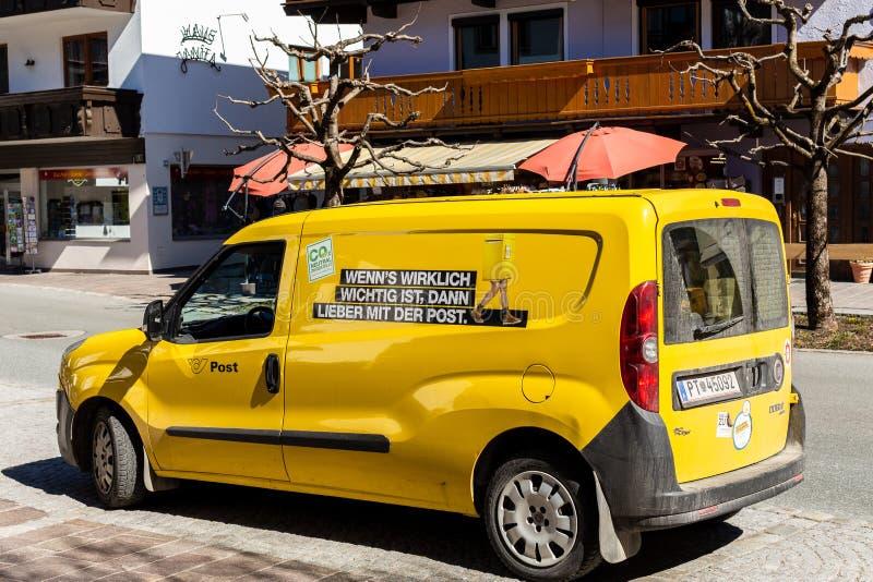 Westendorf Tirol/Österrike: Mars 29 2019: Liten leveransbil av de österrikiska postgångarna från baksidan på en vinkel royaltyfri bild