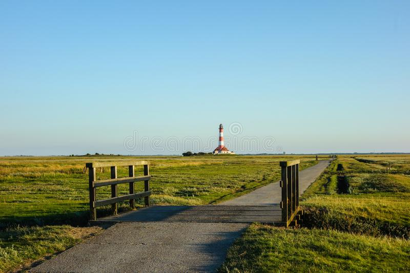 Westerhever lighthouse with path in salt marshes at blue sky. Westerhever lighthouse with path in salt marshes blue sky royalty free stock photography