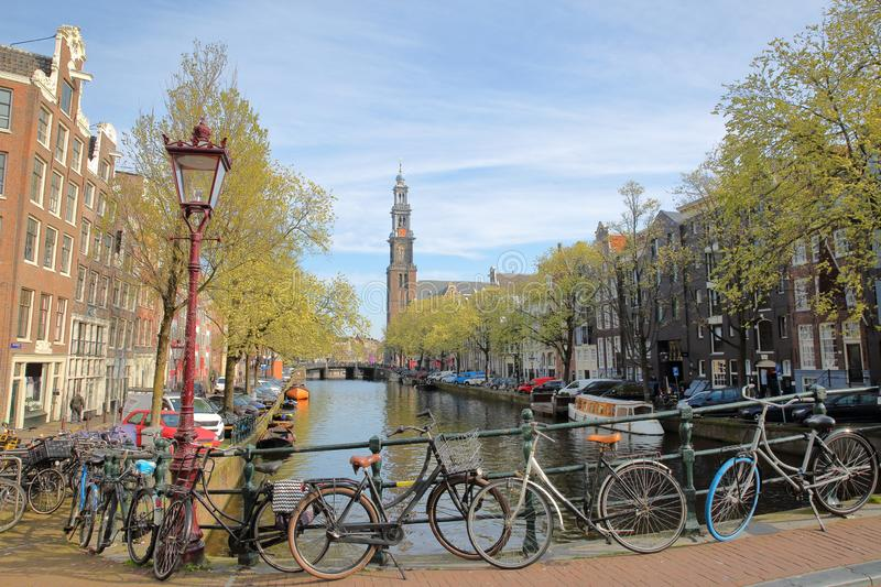 Westerkerk Church clock tower and historic buildings viewed from Reestraat Bridge along Prinsengracht Canal in Amsterdam. Netherlands royalty free stock images